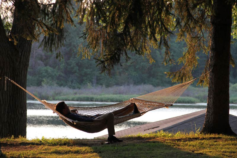 Man relaxing on a hammock at Camp Woodbury